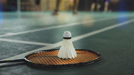 Closeup shot of white badminton shuttlecock and racquet on green floor.