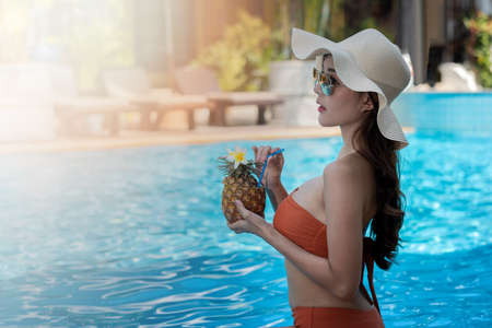 Sexy young asian woman in swimsuits in summer. beautiful woman in orange bikini with hat sitting in swimming pool with tropical drink.