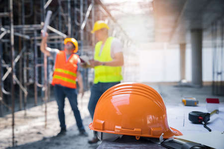 The yellow safety helmet in construction site and construction site worker background safety first concept.