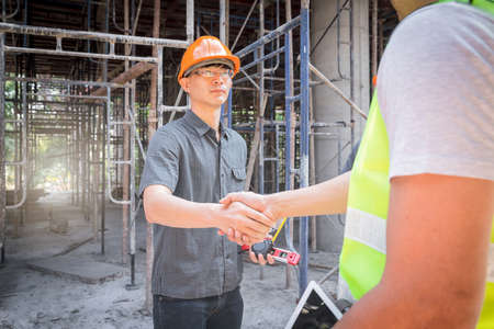 Teamwork, partnership, gesture concept. Builders greeting each other with handshake on construction site. construction workers in protective helmets and vests are shaking hands. Standard-Bild