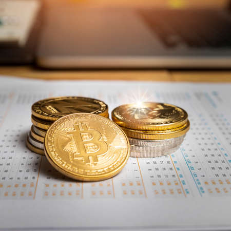 Stack of Various golden and silver of Cryptocurrency on chart or graph paper. New Virtual money concept.