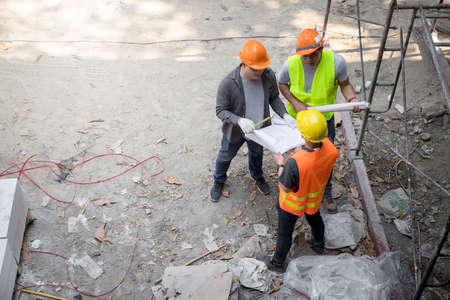 Confident team of architect working together in building construction site. They discussing about new startup project. Architect discuss with engineer about project . Architectural concept.