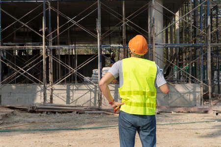Rear view of engineer or contractor standing at a building site. Young businessman construction site engineer. Standard-Bild