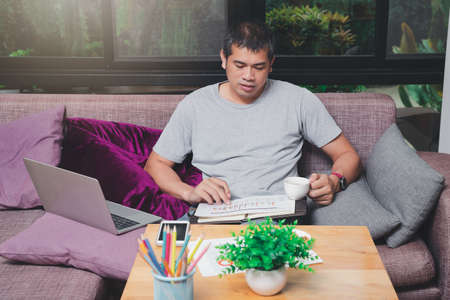 Asian man holding a cup of coffee and working while sitting on sofa in home office.