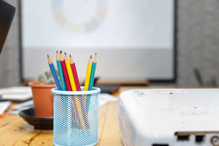 Colorful pencil in box with cactus pot on desk in office.