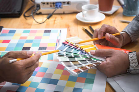 Interior designer chooses a color chart for home design. Graphic designers working on color chart at modern office.