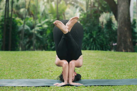 Asian woman practicing yoga in Supported Headstand Pose on the mat in outdoor park.