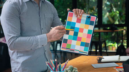 Young man holding and point to a color chart for home design. Graphic designers working on color chart at modern office. Stock fotó