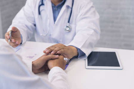 Doctor holding patient's hand for encouragement, empathy, cheering and support while medical examination. Bad news lessening, medicine and health care concept.