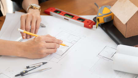 Female architect working on blueprint architects project in office. Stock fotó