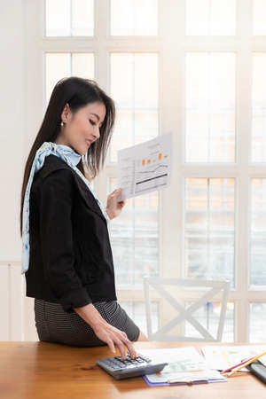 Businesswoman holding business document and using calaulator while standing near the window. Stock fotó