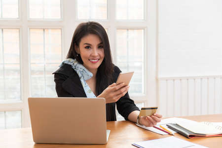 Young asian woman holding credit card and using smartphone for purchase product on internet in home office. Online shopping concept.