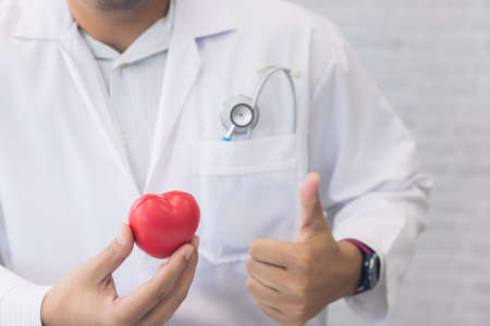 Doctor hands hold a red heart and thumbs up over desk. Concept of health care and medical. Stock fotó