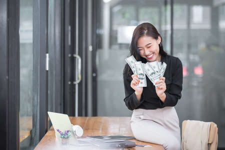 Beautiful young woman holding us dollar money. business, finance, saving, banking and online shopping concept.