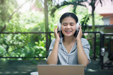 Asian woman wearing headphones listening to music on her laptop. Relaxing time. Lazy worker wasting time at workplace in co-working.