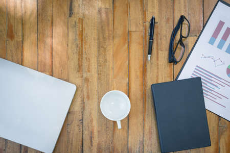 Empty cup of coffee, laptop, notebook, pen, glasses and graph on wooden table. Top view with copy space.