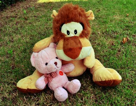 teddy bear love: Teddy bear and lion doll hugging in garden vintage