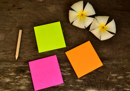 Colorful post it note with Plumeria flower on wooden board