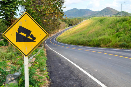 descent: Steep hill descent sign side beautiful road Stock Photo