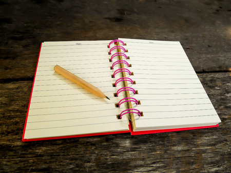 Note book with pencil on wooden table