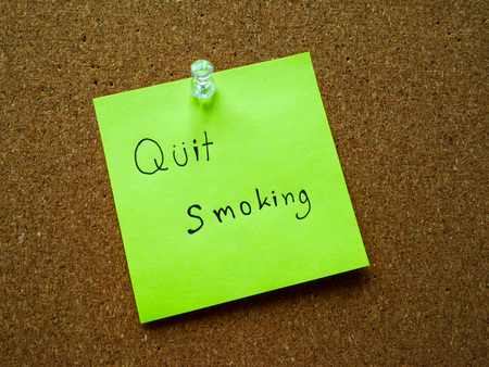 Quit smoking on post note for remind on wooden board