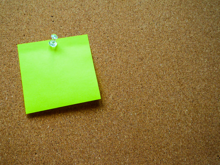 Green post note on wooden board with copy space