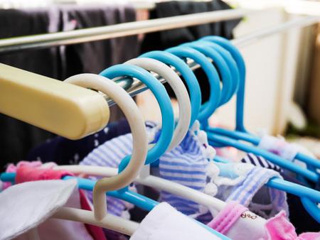Plastic kid hangers on metal rack in home