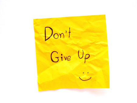 Write don't give up on yellow post note isolated on white background 免版税图像
