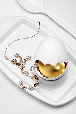 golden jewelry inside broken egg on white egg cup