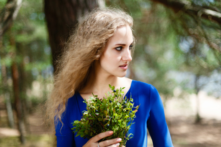Summer portrait of a young girl in the forest with a bouquet of flowers. Spring in the forest or Park. Blue bouquet in girl hands in a blue long dress. Blueberries in the hands close up natural food.