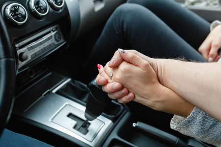 A young couple in love holding hands, holding on the shift lever going into the road trip. A man and a girl go together by car. Young couple holding hands in car. Wedding rings.