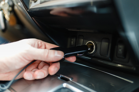 A man connects the device to the cigarette lighter of the car. The man's hand is plugging the car camera or phone adapter into the cigarette lighter into the car.