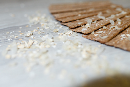 Close-up of dietary loaves laid out in the form of a fan on each other on a wooden table in rice flakes. Dry snacks dietary breakfasts, loaves on a grey wooden table.