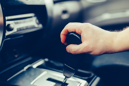 The man hand switches the automatic transmissions close-up. Close-up of the drivers arm includes mode Drive on the gear lever automatic transmission of the car interior parts. Stylish Toned Photo