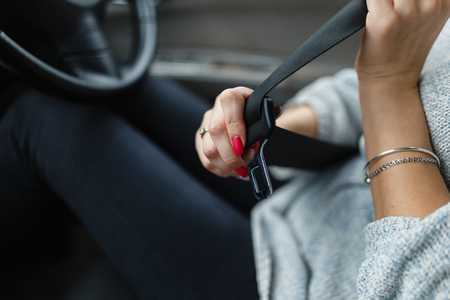 Clasp safety belt in the hands of the girl. Driver girl fasten your seat belt. Close-up Of Females Hand Sitting Inside Car Fastening Seat Belt. Concept of safe driving while driving.