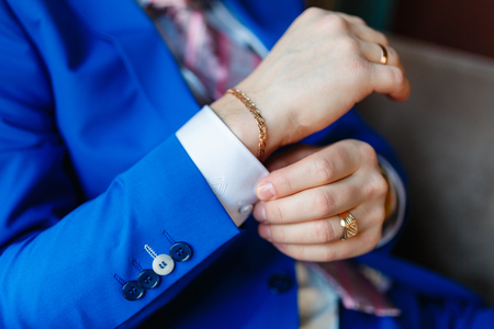 The man sits in an armchair and fixes the cuffs on a white shirt and a stylish blue jacket with expensive gold accessories, watches, rings and rings. The businessman is preparing to meet.