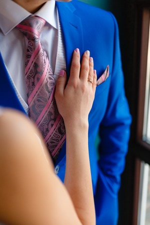 Womens hand on the chest of a man in an expensive suit. A close-up shot of a man in a blue suit while a woman�s hand is resting on his chest