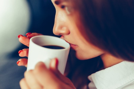 Close-up of the lips of a girl drinking coffee while sitting on the bed. Sunny lazy morning in bed. White mug with hot coffee in the hands of a young girl. Breakfast in bed. Toned photo