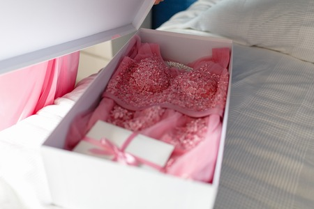 A young girl in a pink robe opens a white box with a bow with a new pink dress inside, unleashes a bow on the gift box. Surprise or gift on the bed in the bedroom.