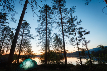 Night landscape with a tent in the forest near lake. The light from the lantern in a tent. Camping in the wild nature. Stockfoto