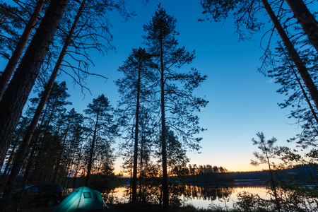 Night landscape with a tent in the forest near lake. The light from the lantern in a tent. Camping in the wild nature. Stockfoto - 106913694