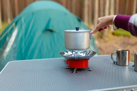 Female hand is cooking in an aluminum pot meals on a portable gas burner on background in the camping in the forest. Women hand hold a saucepan on a gas burner (camping stove) in background green tent