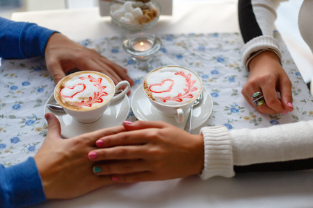 Young couple drink coffee in love clasping hands across the table in cafe, closeup. Romantic background, two cups of coffee and hands of couple in love on date. Romantic dinner in valentines day.