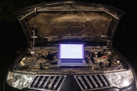 Laptop torque figures and horsepower is the engine of the vehicle for diagnostics and configuration. Diagnostic machines is ready for use with the car. Broken car in auto repair shop. Auto service. Фото со стока