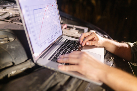 Closeup hands of mechanic with the help of diagnostic machines is ready for use with the car. Laptop torque figures and horsepower is the engine of the vehicle for diagnostics and configuration.