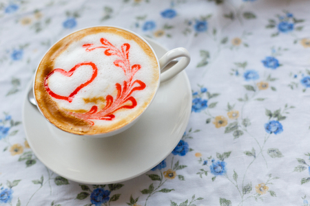A Cup of hot cappuccino with a pattern of a red heart on the table with a tablecloth in a flower in a coffee shop. Close-up and blur.