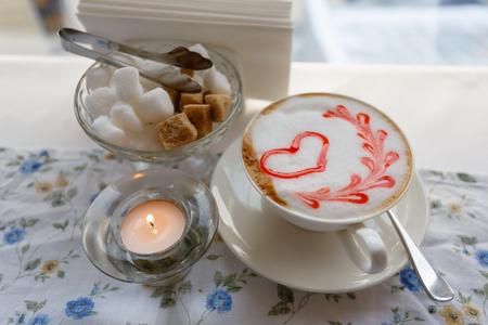 A Cup of hot cappuccino with a pattern of a red heart on the table with a tablecloth in a flower in a coffee shop. Near sugar bowl with sugar and a burning candle. Close-up and blur.