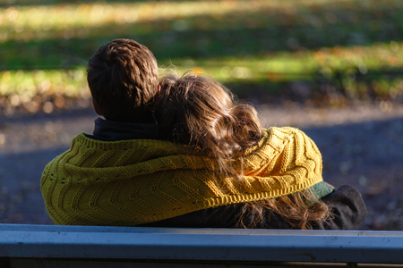 The young couple is deeply in love, sitting on a wooden bench enjoying a tender moment in a close embrace on a bench overlooking a tranquil Park. The young couple is covered with a warm yellow scarf. Banco de Imagens