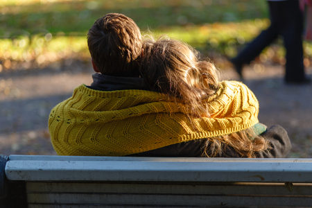 The young couple is deeply in love, sitting on a wooden bench enjoying a tender moment in a close embrace on a bench overlooking a tranquil Park. The young couple is covered with a warm yellow scarf. Фото со стока