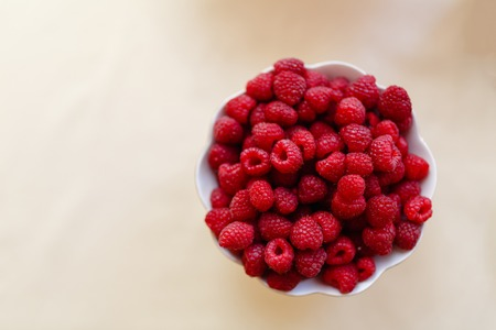 Red fresh raspberries in white bowl on light rustic wood background. Top view with copy space. Selective focus. Vegetarianism Фото со стока